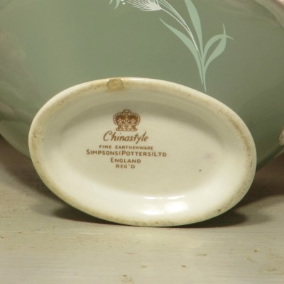 An elegant green and white gravy boat with a hand painted wheat design.