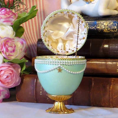 Feberge Style Decorated Goose Egg Trinket Box Signed Sue Harvey.  A pretty hand decorated goose egg silk lined  trinket box on a gold tone metal base with metal chain hinge.  A lovely addition to a collection.