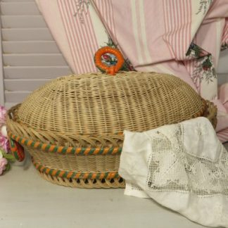Wicker Sewing Basket with Orange and Green Edging.  Maybe not just for sewing?  This pretty little basket with lid could be used in your kitchen