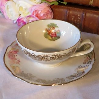 Royal Porcelain Romantic Demi Tasse Duo. A pretty coffee cup and saucer edged in swirls of gold with an image of a courting couple on the inside